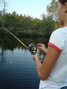 A young fishergirl learned to hook a worm and fish for the first time